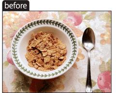 テーブルにのったコーンフレークの入ったお皿とスプーンの写真