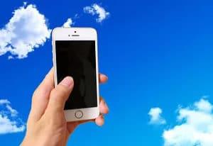 スマートフォンを持つ手の背景に空を合成した画像